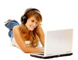 Casual student listening to music on the computer while studying isolated over a white background