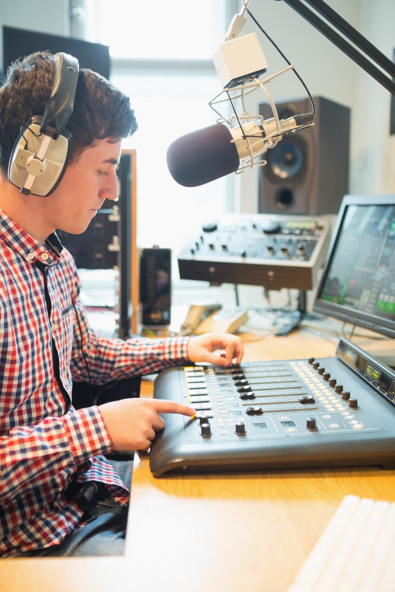 radio-host-wearing-headphones-operating-sound-mixer-on-table-in-studio