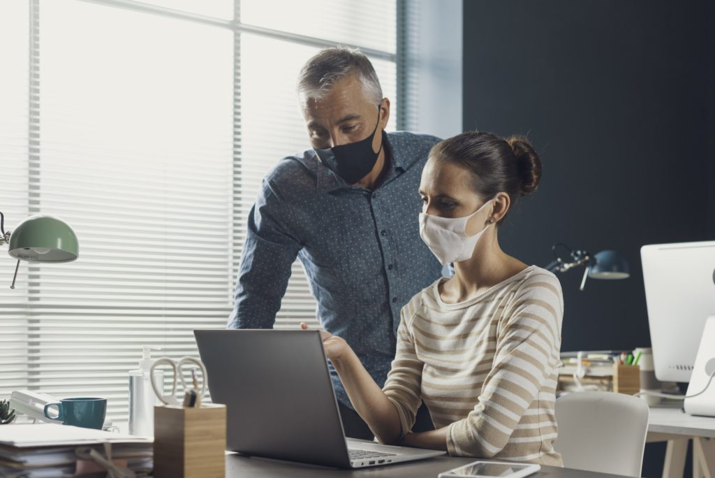 Business people working together and wearing face masks