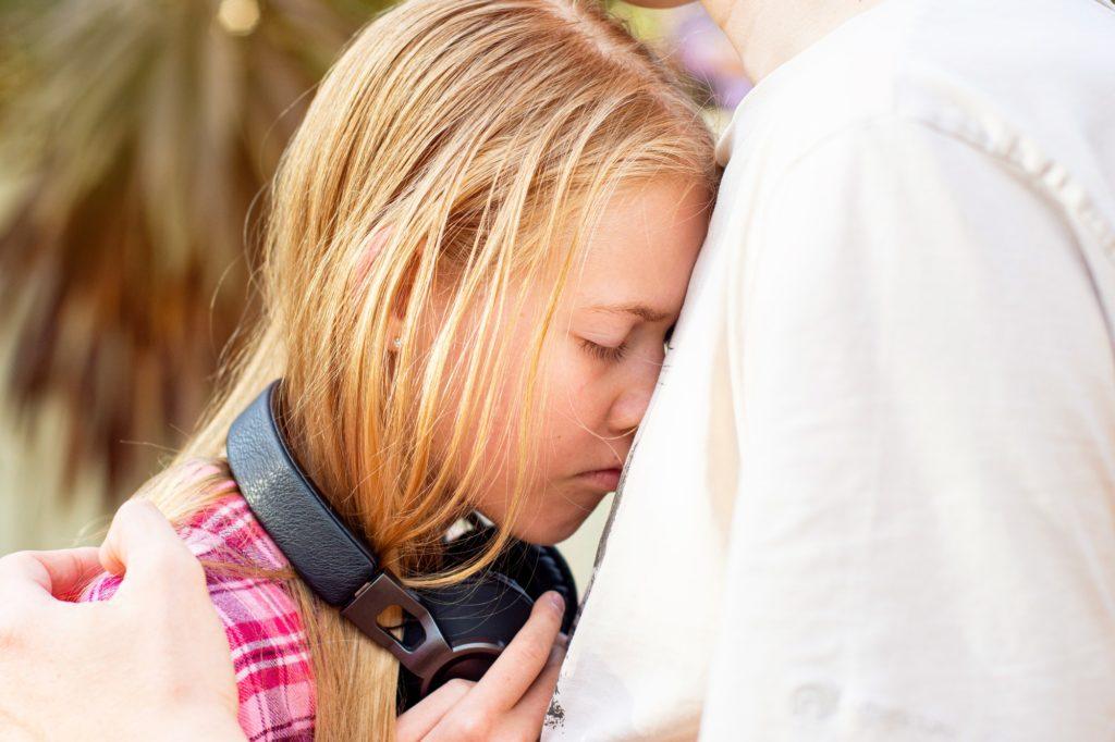 Father hugs his depressed teenage daughter wearing headphones