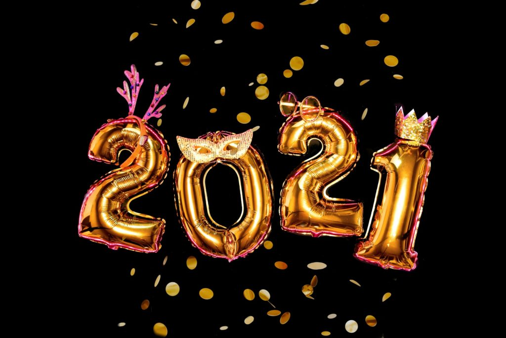 Gold numbers 2021 on black background in carnival accessories, new year party