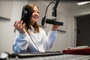 Female Jockey Communicating On Microphone In Radio Studio