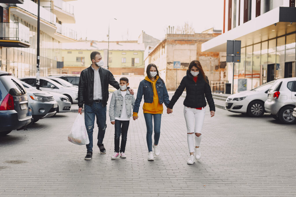 """<a href=""""https://www.pexels.com/photo/young-family-in-medical-masks-walking-along-parking-4127449/"""" target=""""_blank"""" rel=""""noopener"""">Gustavo Fring</a> at Pexels"""