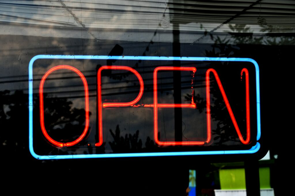 Neon OPEN sign in teal and orange - Yes, we're open for business