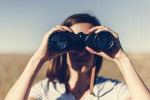 Traveler spying through binoculars