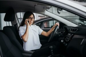 Businesswoman talking on the phone in car.