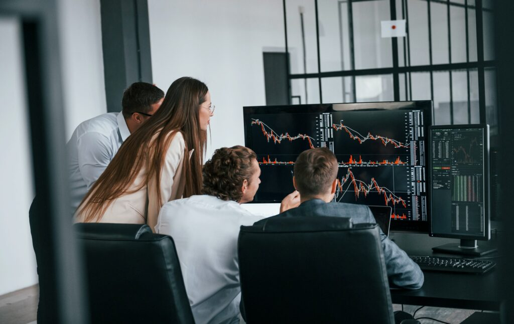Tracks the graphs. Team of stockbrokers works in modern office with many display screens