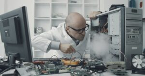 Technician damaging a computer with a screwdriver