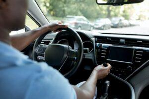 Unrecognizable black man driver turning on radio in auto